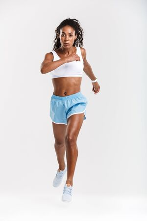 Full length of an attractive healthy confident african sportswoman running isolated over white background 版權商用圖片