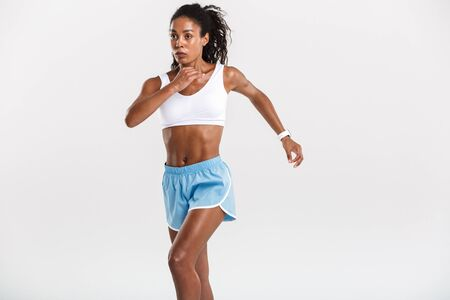 Portrait of an attractive healthy confident african sportswoman running isolated over white background 版權商用圖片