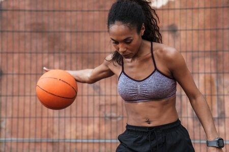 Attractive young african sportswoman playing basketball at the playground outdoors
