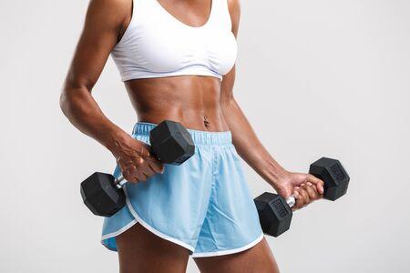 Abgeschnittenes Bild einer attraktiven, gesunden, selbstbewussten afrikanischen Sportlerin, die mit Hanteln auf weißem Hintergrund trainiert