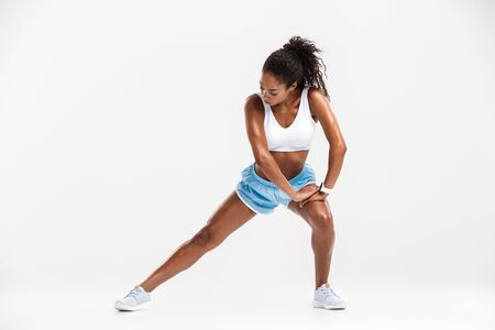 Attractive young healthy african fitness woman doing stretching exercising isolated over white background