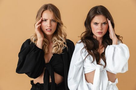Portrait of two sick women in black and white clothes looking at camera while rubbing their temples isolated over beige background Фото со стока