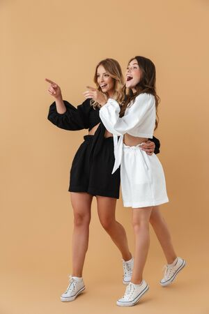 Portrait of two joyful women in black and white clothes hugging while pointing fingers aside at copyspace isolated over beige background