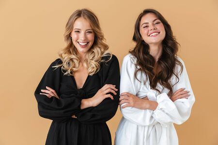 Portrait of two happy women in black and white clothes smiling at camera with arms crossed isolated over beige background Фото со стока