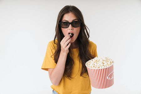 Image of concentrated young woman isolated over white wall background in 3d glasses eat popcorn watch film.