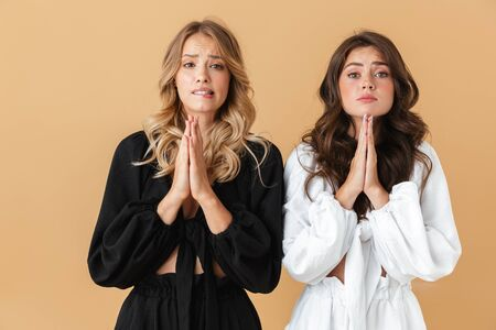 Portrait of two sad women in black and white clothes looking at camera while holding palms together isolated over beige background