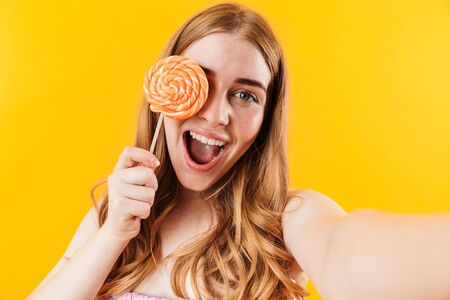 Photo of a cheery positive young cute teenage girl posing isolated over yellow wall background holding sweet candy lollipop take a selfie by camera.