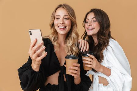 Portrait of two smiling women in black and white clothes using cellphones while drinking coffee takeaway isolated over beige background Zdjęcie Seryjne