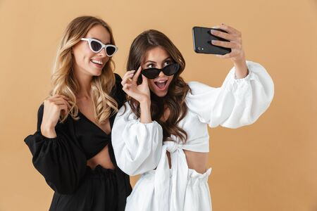 Portrait of two smiling women in sunglasses taking selfie photo on smartphone isolated over beige background Zdjęcie Seryjne
