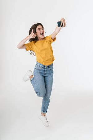 Image of a positive optimistic young emotional woman jumping isolated over white wall background take a selfie by mobile phone showing thumbs up. Stockfoto