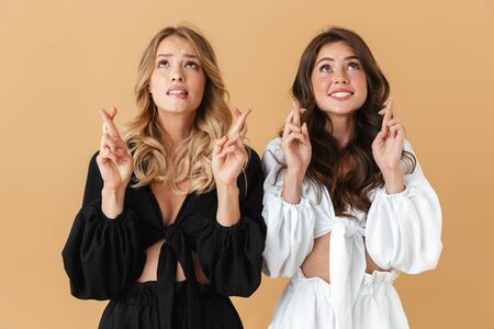 Portrait of two nice women in black and white clothes looking upward with crossed fingers isolated over beige background