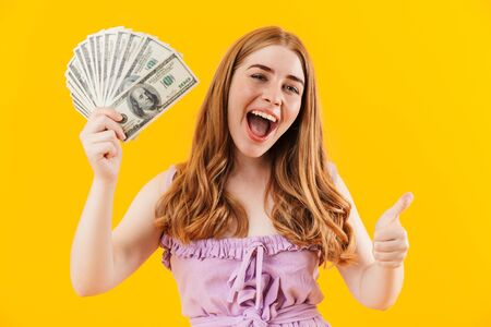 Photo of a young positive happy girl isolated over yellow wall background holding money showing thumbs up gesture.
