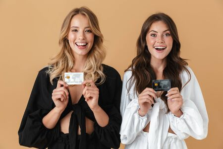 Portrait of two delighted women in black and white clothes smiling while holding credit cards isolated over beige background