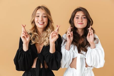 Portrait of two pretty women in black and white clothes looking upward with crossed fingers isolated over beige background