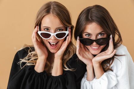 Portrait closeup of two young women in sunglasses smiling and looking at camera isolated over beige background