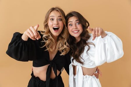 Portrait of two excited women in black and white clothes pointing fingers at camera isolated over beige background Фото со стока