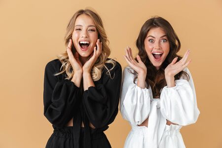 Portrait of two excited women in black and white clothes looking at camera with throwing up hands isolated over beige background