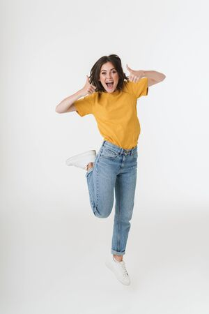 Image of a surprised excited young emotional woman jumping isolated over white wall background with thumbs up. Banco de Imagens