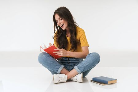 Image of happy cheery young woman isolated over white wall background writing notes in notebook.