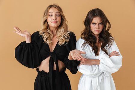 Portrait of two angry women in black and white clothes poising with crossed arms isolated over beige background Banco de Imagens