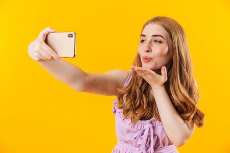 Photo of a young cute pleased girl isolated over yellow wall background take selfie by mobile phone blowing kisses.