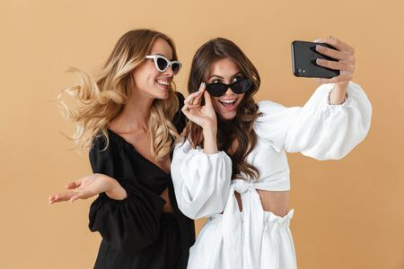 Portrait of two cheerful women in sunglasses taking selfie photo on smartphone isolated over beige background