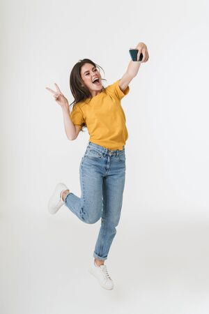 Image of a cheery young emotional woman jumping isolated over white wall background take a selfie by mobile phone showing peace. 版權商用圖片