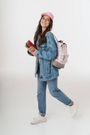 Photo of teenage student girl wearing denim clothes smiling and holding studying books isolated over white background