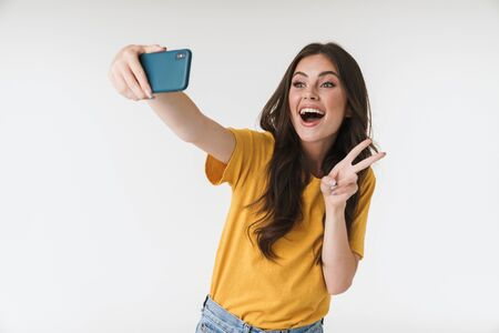 Image of pleased brunette woman laughing and showing peace sign while taking selfie photo on cellphone isolated over white background 版權商用圖片