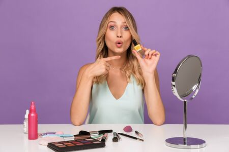Photo of a cute shocked young woman posing isolated over purple wall background with cosmetics with mirror holding nail polish gel pointing. 写真素材 - 133582657