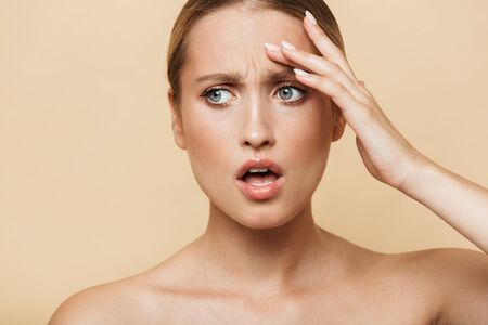 Beauty image of shocked emotional blonde woman posing naked isolated over beige wall background.