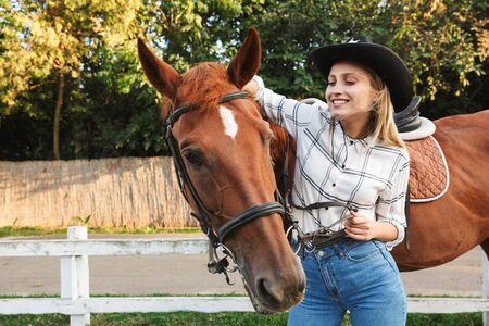 Beautiful smiling young blonde woman petting a horse at the horse yard Stock Photo