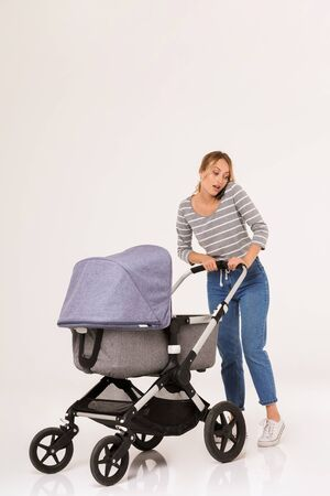 Full length of a beautiful young woman standing with a baby pram isolated over white background, talking on mobile phone
