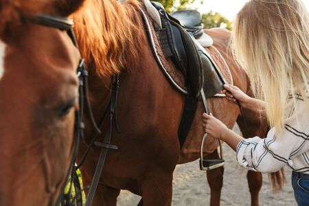 Beautiful young blonde woman petting a horse at the horse yard, fixing saddle