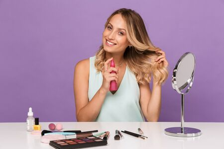 Photo of a cheery positive young woman posing isolated over purple wall background with cosmetics with mirror using hair spray. 免版税图像