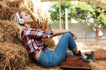 Smiling young blonde cowgirl relaxing on a haystack at the barn, listening to music with wireless headphones