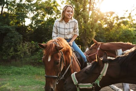 Smiling attractive young blonde girl riding a horse at the horse yard