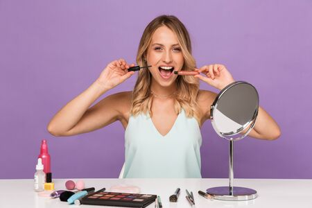 Photo of an emotional young woman posing isolated over purple wall background with cosmetics with mirror holding lip gloss.