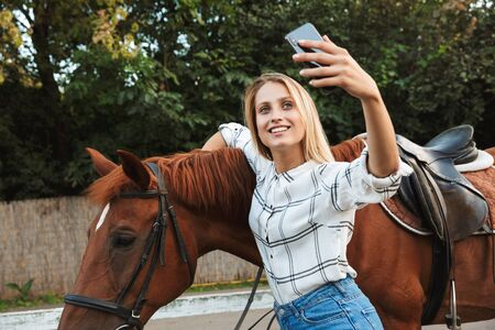 Beautiful smiling young blonde woman petting a horse at the horse yard, taking a selfie