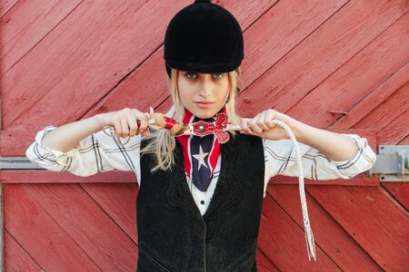 Smiling blonde girl jockey standing at the barn, holding horsewhip