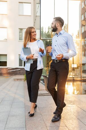 Image of a young cheery man and woman businesspeople outside at the street near business center walking holding clipboard and cup of coffee talking with each other.