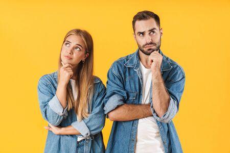 Portrait d'un séduisant jeune couple pensif portant des vêtements décontractés isolés sur fond jaune, regardant dans les deux sens