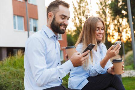 Imagen de un hombre y una mujer de colegas felices jóvenes empresarios sentarse afuera en la calle usando teléfonos móviles.