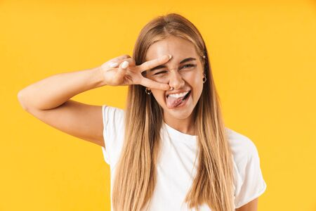 Cheerful young girl wearing casual clothing standing isolated over yellow background, showing peace gesture Reklamní fotografie - 133067193