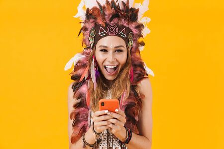 Image of emotional pleased young happy indian woman in carnival suit isolated over yellow wall background using mobile phone.