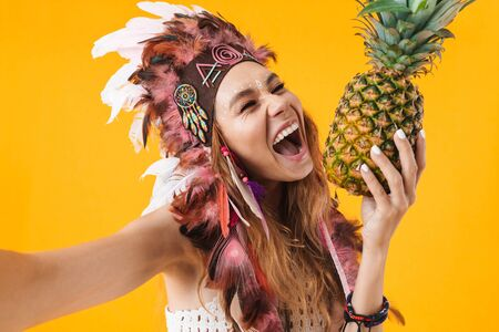 Portrait of delighted woman in headdress of feathers taking selfie photo and holding pineapple isolated over yellow background