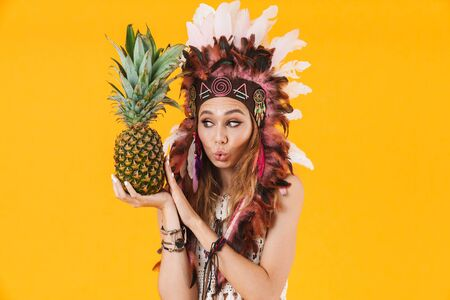 Portrait of amusing woman in headdress of feathers holding pineapple and grimacing isolated over yellow background Stock fotó