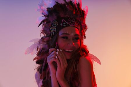 Portrait of cheerful nice woman in headdress of feathers laughing and looking aside isolated over violet neon background