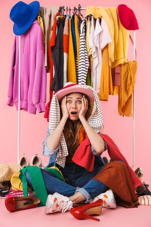 Photo of shocked young woman wearing hat sitting near bunch of clothes and shoes isolated over pink background Stock Photo