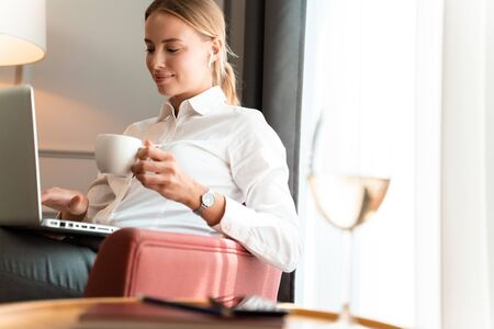 Image of a young beautiful cute pleased positive blonde business woman sit indoors in cafe using laptop computer drinking coffee.